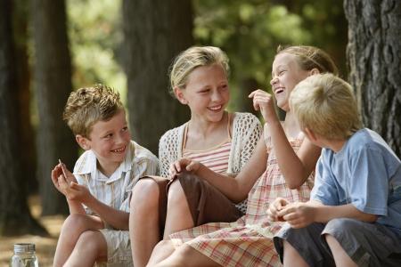 niÑos hablando: Cuatro niños (7-9) que se sienta en la risa del bosque.