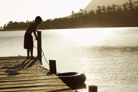 mischeif: Boy (7-9) standing on dock pulling in float tube.