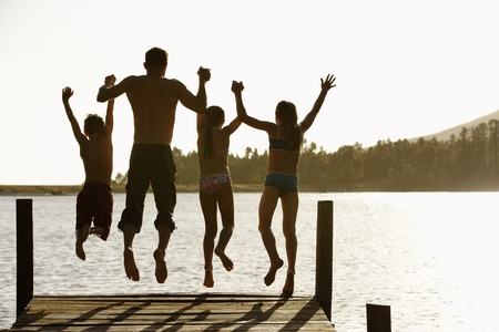 late summer: Rear view of father and children jumping off a pier holding hands