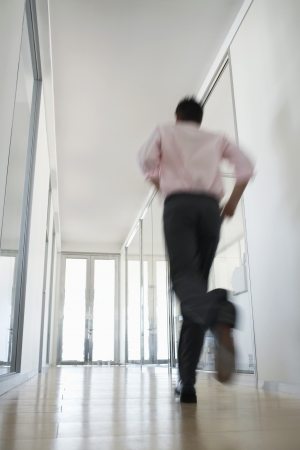 running pants: Businessman Running in Corridor low angle back view. LANG_EVOIMAGES