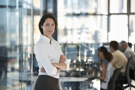 glass partition: Businesswoman standing in office with group of office workers in background.
