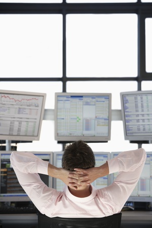 Businessman with Hands Behind Head watching computer screens back view. Stock Photo - 19465737