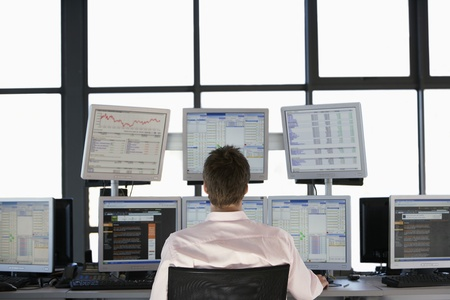 Businessmen sitting at desk watching computer screens back view. Stock Photo - 19521720