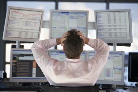 Unternehmer gerade Computer-Bildschirme mit den Händen auf den Kopf nach hinten zu sehen.