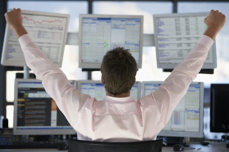 Businessman watching computer screens with arms raised back view. Stock Photo