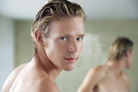 bare chested: Man in bathroom looking over shoulder portrait