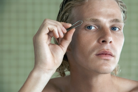 body concern: Man plucking eyebrows close-up