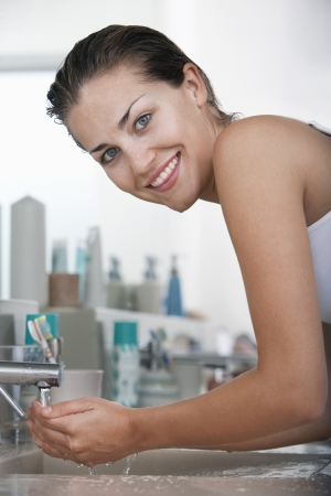 washing face: Woman washing face in bathroom LANG_EVOIMAGES