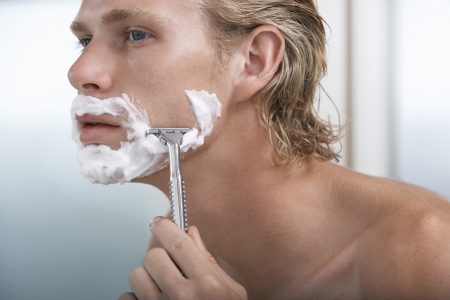 young adult man: Man shaving face in bathroom close-up