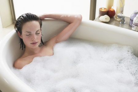 elevated view: Young woman relaxing in bubble bath eyes closed. elevated view