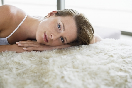 spaghetti strap: Woman relaxing on bed portrait