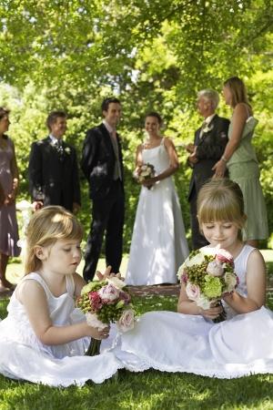 Deux jeunes filles assises sur la pelouse tenue bouquets mariée et le marié en arrière-plan