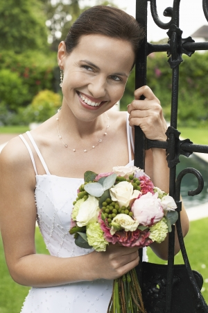 wedding bouquet: Mid adult bride leaning on gate holding bouquet looking away portrait