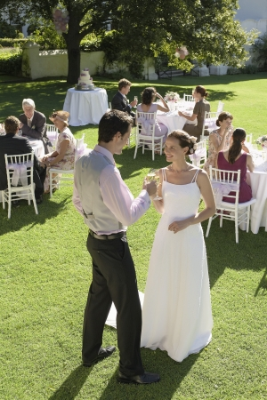 two people with others: Mid adult bride and groom in garden toasting among wedding guests