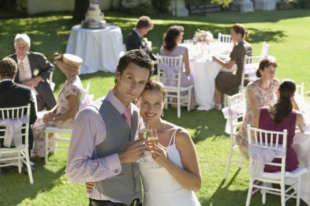two people with others: Mid adult bride and groom in garden among wedding guests holding wineglasses embracing LANG_EVOIMAGES