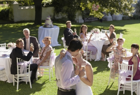 two people with others: Mid adult bride and groom in garden among wedding guests holding wineglasses kissing