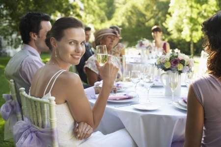 wedding party: Bride sitting at wedding table holding wineglass smiling