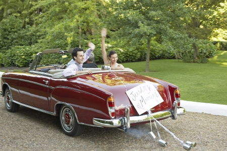 road of love: Mid adult bride and groom in vintage car waving hands