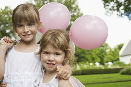 Two Girls with Party Balloons in Garden Stock Photo