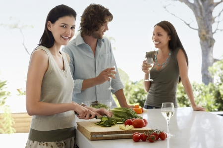 one person with others: Friends talking  drinking wine preparing food at a dinner party outside