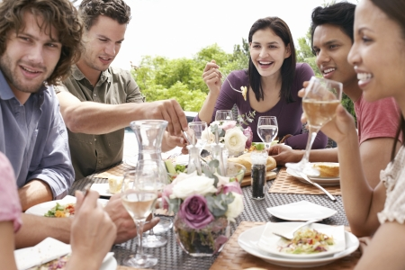 medium group of people: Friends eating drinking and socialising at table outdoors