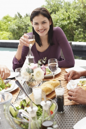 one person with others: Young Woman Drinking Wine outdoors at a dinner party LANG_EVOIMAGES