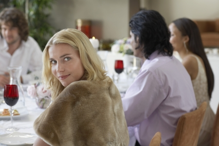 formal dinner party: Young woman sitting at table of formal dinner party LANG_EVOIMAGES