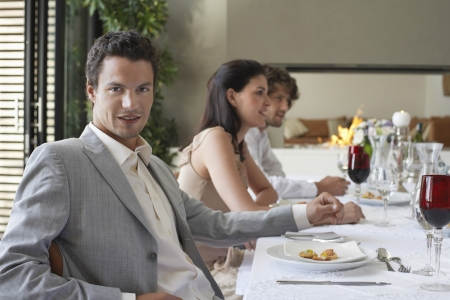 formal dinner party: Young stylishly dressed man sitting at table of formal dinner party smiling LANG_EVOIMAGES