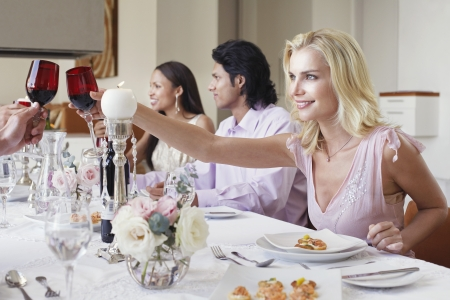 dinner wear: Young woman in dress toasting at formal dinner party