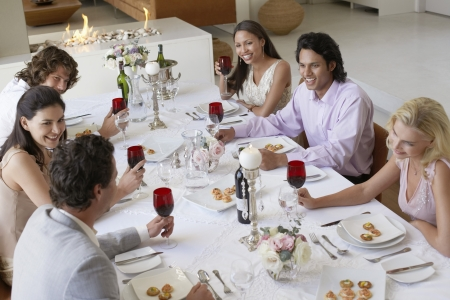dinner wear: Friends sitting together at Dinner Party drinking and socialising elevated view