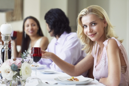 dinner wear: Young woman in dress sitting at table of formal dinner party
