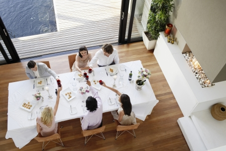 dinner wear: Friends toasting across table at a formal dinner party high angle view