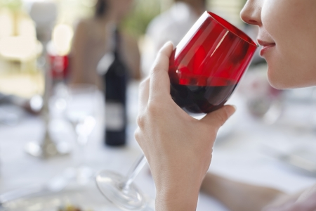 one person with others: Young woman drinking from wineglass close-up side view LANG_EVOIMAGES
