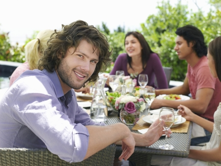 Young man enjoying outdoor dinner party smiling to camera Stock Photo - 19521867