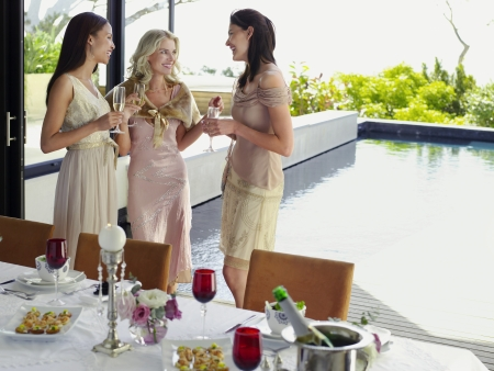 dinner wear: Young female Friends drinking and socialising near pool at Dinner Party