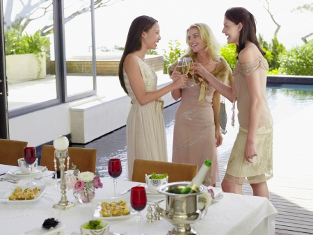 formal dinner party: Young female Friends drinking and socialising near pool at Dinner Party