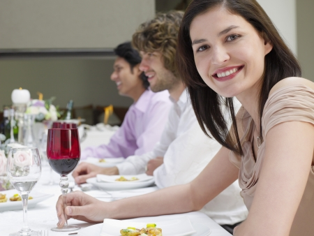 formal dinner party: Young woman in dress sitting at table of formal dinner party side view