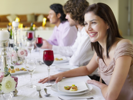 dinner party people: Smiling young woman at dinner party