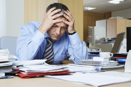 mature business man: Businessman sitting at desk with head in hands