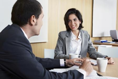 two people talking: Businesspeople having meeting in office