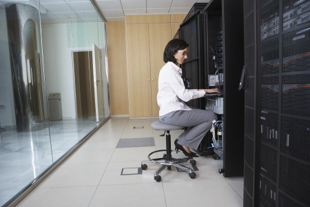 it technology: Female technician working in server room