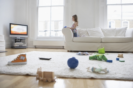 living: Girl Watching Television in Messy Living Room