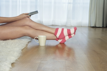 crossed legs: Woman Using Television Remote Control LANG_EVOIMAGES