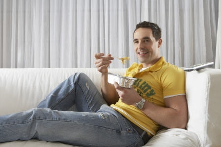 Young Man Eating Takeout Food and Watching Television