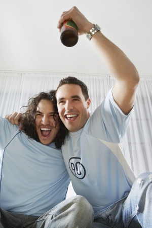 raise your hand: Two Excited Young Men Drinking and Watching Television LANG_EVOIMAGES