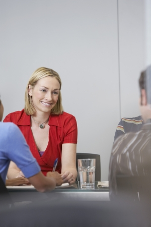 one person with others: Office workers sitting at conference table