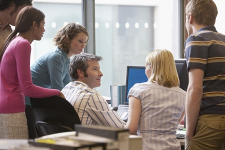casual meeting: Office workers standing around colleague using computer back view