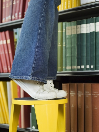 exerting: Student Looking for Book in Library