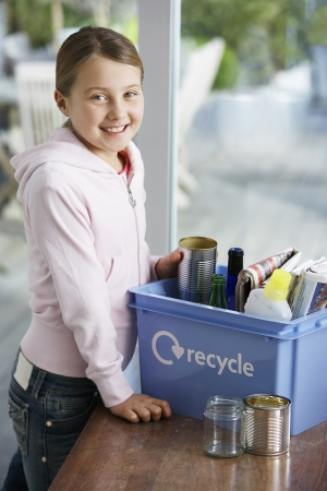 managing waste: Pre-teen Girl Recycling Household Waste