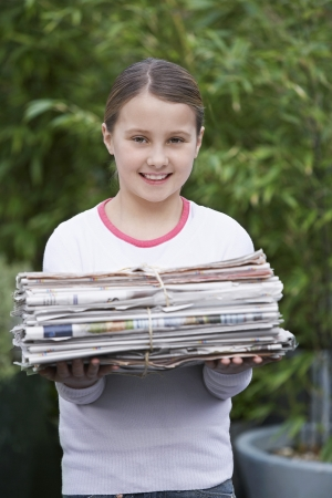 domestic task: Pre-teen Girl Recycling Newspapers